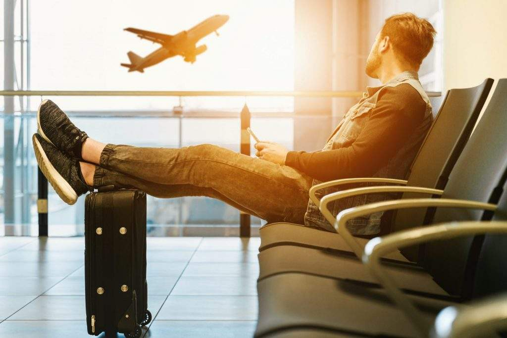 man sitting watching plane take off